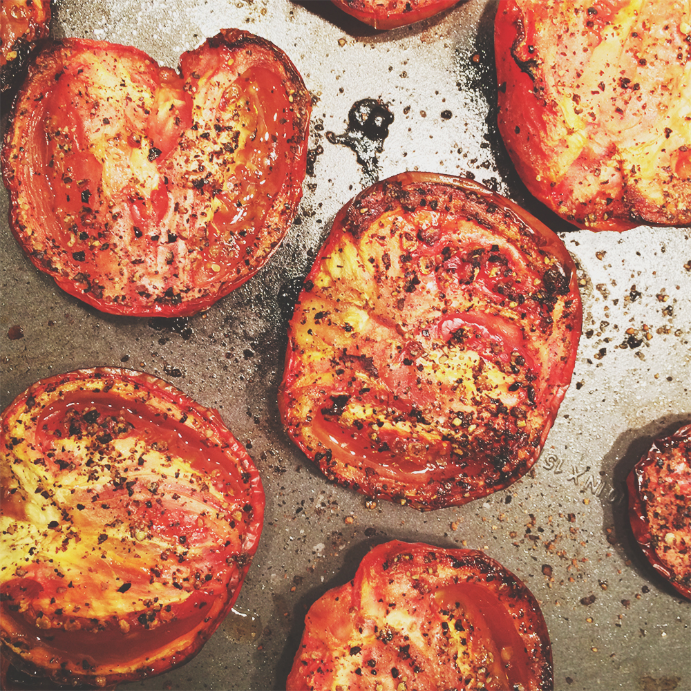 A sheetpan of halved tomatoes, roasted to perfection.