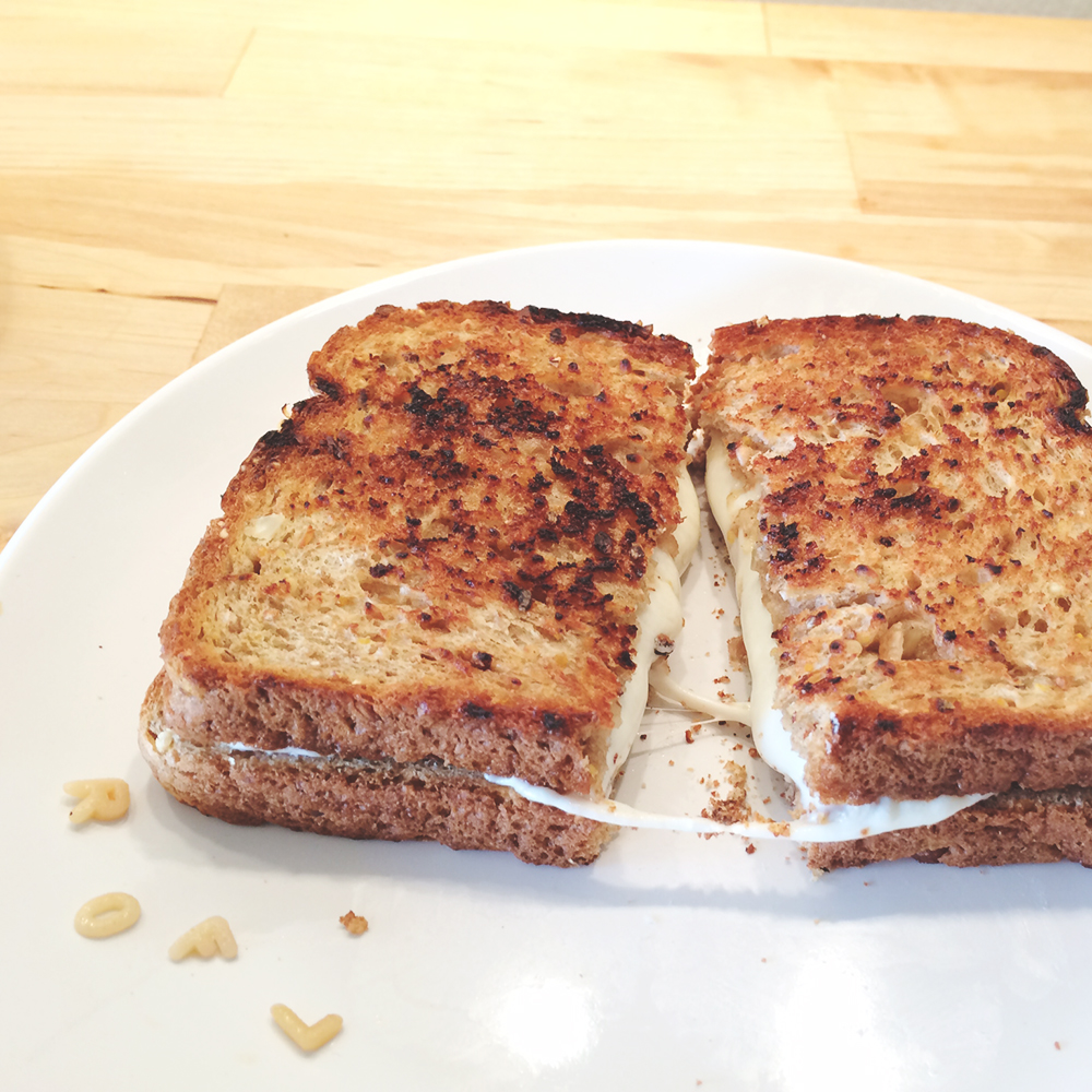 "A grilled cheese sandwich on a plate. The sandwich is cut in half and the cheese is being ""pulled."" The ROFL letters are now on the plate."