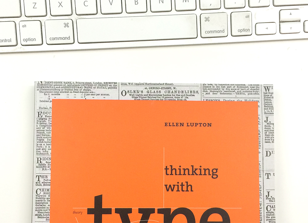 A photo of Ellen Lupton's book Thinking with Type peeking out from the bottom on a white table.