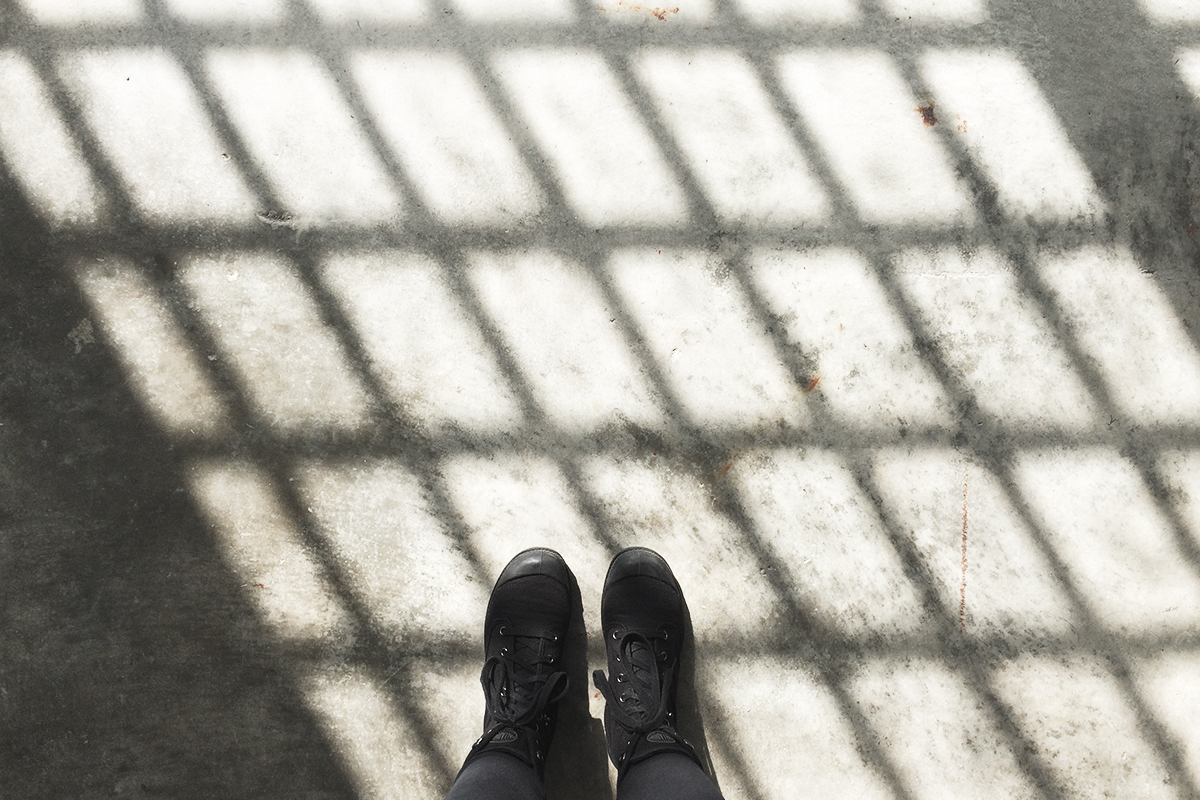 Photo of my feet on the floor of Alcatraz, the window pane casting a shadow