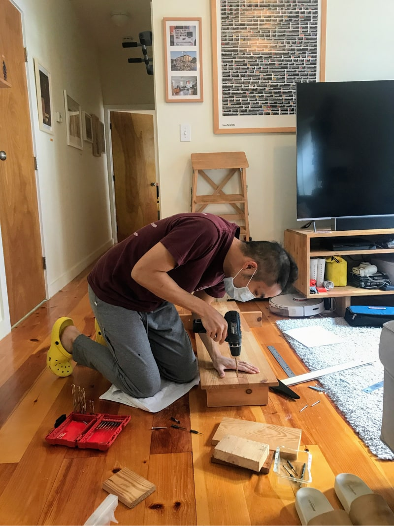 Kevin making his shelf. He is kneeling on the living room floor and drilling a pilot hole into the top plank and one of the legs.